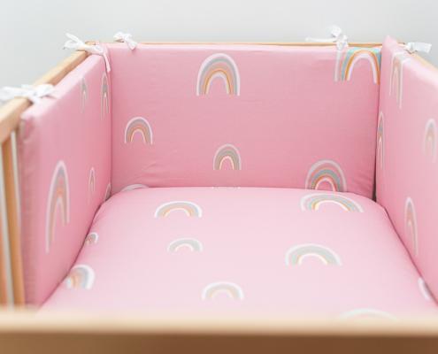 Protectores de cuna rosa a juego con las sábanas