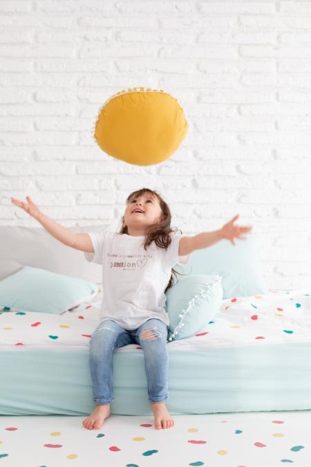 Ropa de cama, cojines varios colores y alfombra colección huellas