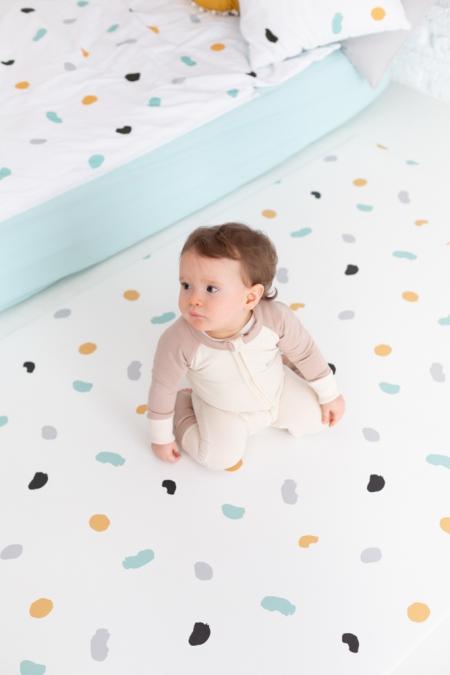 Detalle de cojín, ropa de cama y alfombra colección huellas gris, amarillo, negro y mint