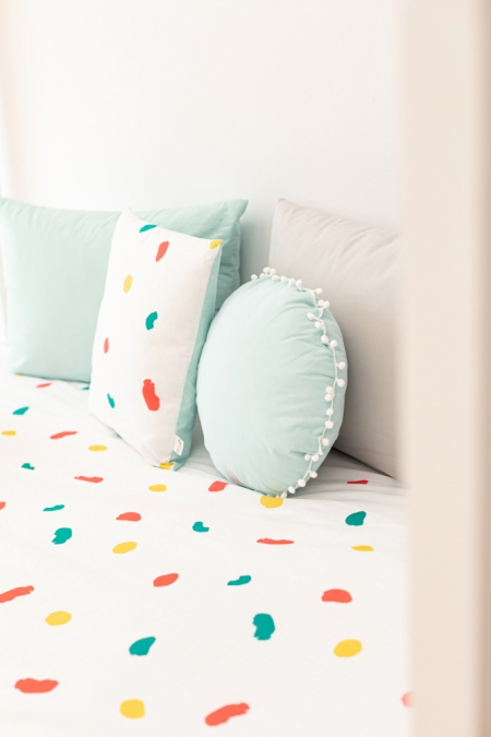 Almohada infantil con borlas mint